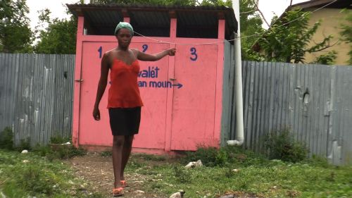 Woman at Leogane camp saying the latrines behind her are full and smell foul. Credit: Haiti Grassroots Watch