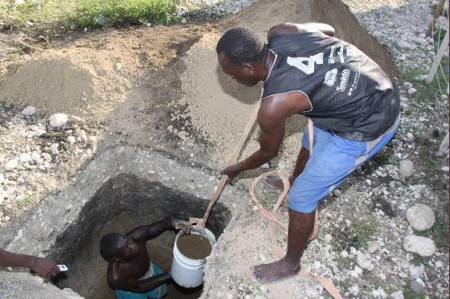 Gérald Saintilimé and Gary Mathieu digging a septic pit at the Tabarre Issa camp. Credit: Fritznelson Fortuné