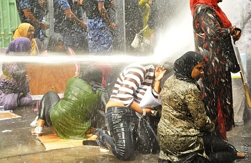 Maldivian women brave water cannon at a protest rally.  Credit: