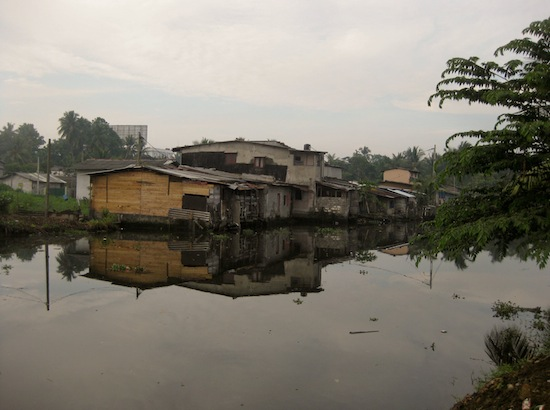 In some parts of Colombo, informal housing structures, or slums, are built right on waterways.  Credit:  Amantha Perera/IPS