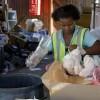 Recycling cooperative member Andiswa Konco sorts garbage.  Credit: Kristin Palitza/IPS