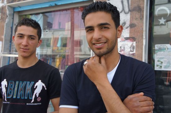 Abdullah Aldiamy (right) outside his family shop at Omar Zerti's occupied building. Credit: Rebecca Murray/IPS.