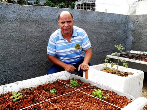 Luiz Alberto de Jesus with the newly sown planters on his balcony in the Babilônia favela. Credit: Fabíola Ortiz/IPS