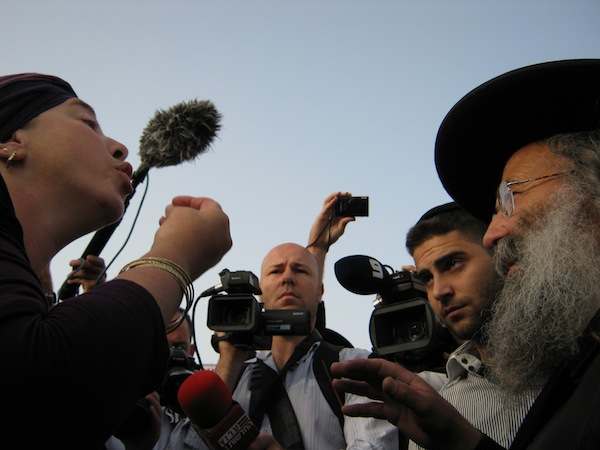 Ultra-Orthodox worshipper Jenny Menashe argues with Rabbi Nahum Weiss. Credit: Pierre Klochendler/IPS