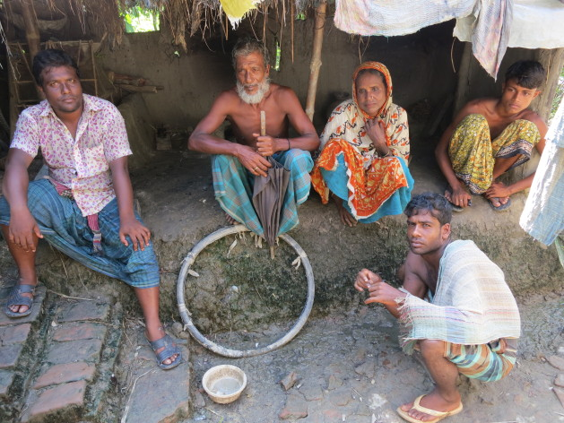 The now landless family of Abdusattar Jaman (holding umbrella). Credit: Robert Stefanicki/IPS.