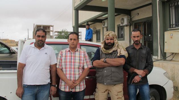Militia commander Ziad Zabala (with a beard) poses next to three policemen at the entrance to the Jadu Police station. Credit: Karlos Zurutuza/IPS