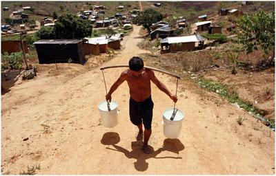 Man hauls water at the Chico Mendes landless peasant camp in Pernambuco, Brazil. Credit: Alejandro Arigón/IPS