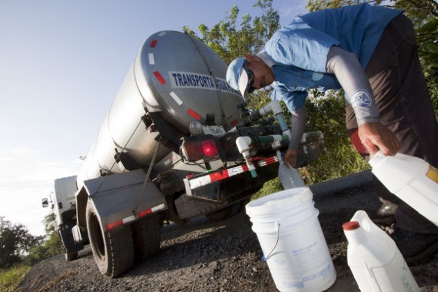 An employee of Costa Rica's water and sanitation utility, AyA, fills the containers of local residents in Milano de Siquirres, who depend on water from tanker trucks because the local tap water has been polluted since August 2007. Credit: Courtesy Semanario Universidad