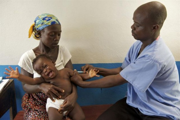 A baby cries in his mother's lap while being inoculated against measles by Vaccinator Joseph Kamara, at Tagweh Town Community Clinic in Bomi County, Liberia. Credit: UNICEF