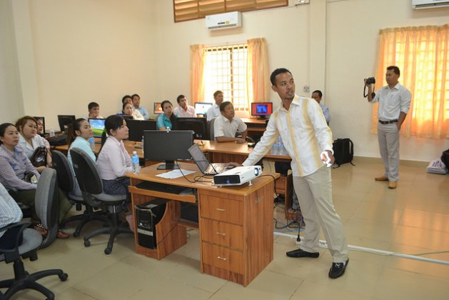 Srun Srorn, a trainer for the E-learning project, walks teachers at Koh Kong High School in Cambodia through a new online sexual education curriculum. Credit: Michelle Tolson/IPS
