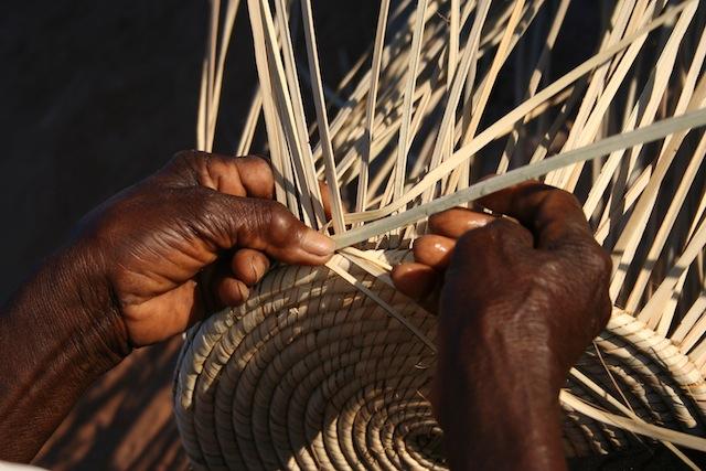 Grace Ngwenya, a skilled weaver from Zimbabwe's Lupane District, deftly threads palm strands into a sturdy basket. Credit: Busani Bafana/IPS