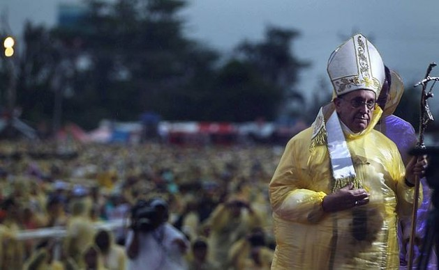 Pope Francis, wearing a yellow raincoat, celebrates mass amidst heavy rains and strong winds near the Tacloban Airport Saturday, January 17, 2015. After the mass, the Pope visited Palo, Leyte to meet with families of typhoon Yolanda victims. The Pope visit to Leyte was shortened due to an ongoing typhoon in the area. Credit: Malacanang Photo Bureau/public domain