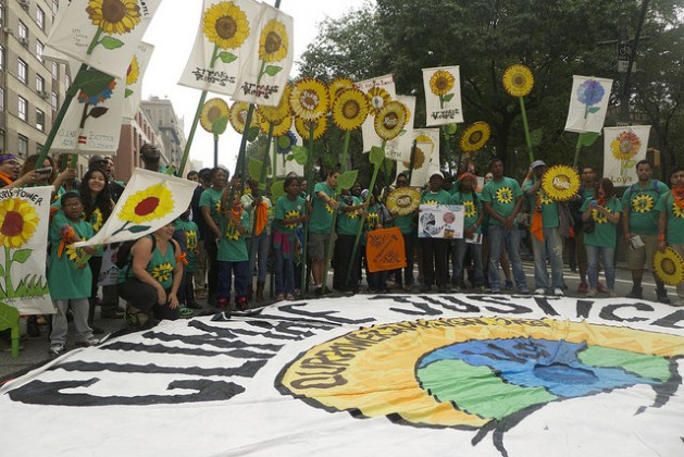 """Campaigners at the September 2014 NYC Climate March say, """"We need a cooperative model for climate justice."""" Credit Roger Hamilton-Martin/IPS"""