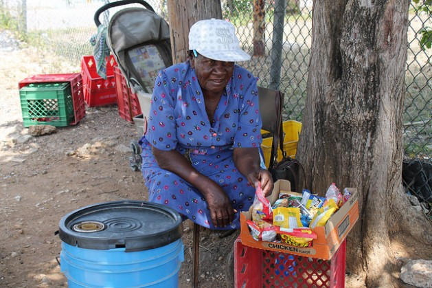 Seventy-year old Elise Young's small box of mixed sweets and biscuits and the plastic bucket containing some ice and a handful of drinks is hardly enough to pay the 18-dollar electricity bill each month and buy food. Credit: Zadie Neufville/IPS