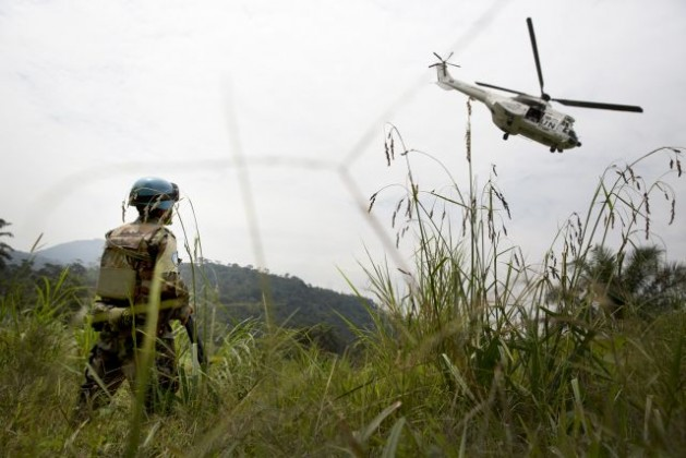 A Uruguayan peacekeeper with UN Organization Stabilization Mission in the Democratic Republic of the Congo (MONUSCO) watches as the helicopter carrying Under-Secretary-General for Peacekeeping Operations, Hervé Ladsous, makes its way back toward Goma after Mrs. Ladsous' visit in Pinga, North Kivu Province. Credit: UN Photo/Sylvain Liechti