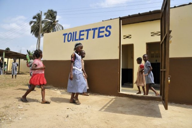 """Children investigate their community's newly improved toilets, one of UNOCI's """"quick impact projects"""" (QIPS) which supported the rehabilitation of schools and toilets in Abidjan. Credit: UN Photo/Patricia Esteve"""