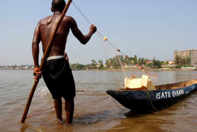 Fishermen use basic wooden canoes to set nets off the coast of Freetown, Sierra Leone. Economies that are dependent on fisheries will be hit hard by warming oceans. Credit: Travis Lupick/IPS