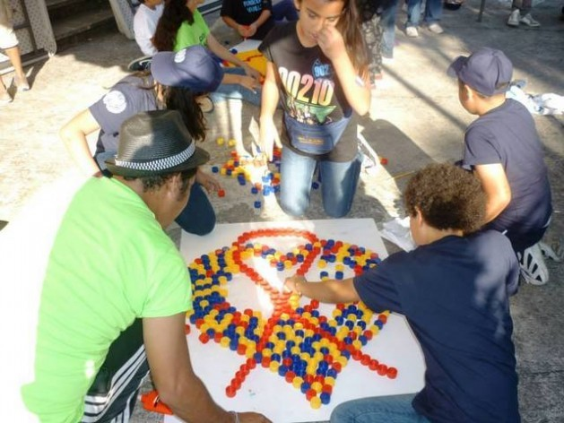 A group of children use bottle caps to create the red ribbon that symbolises the fight against AIDS, in one of the awareness-raising activities carried out in Latin America. Credit: UNAIDS Latin America