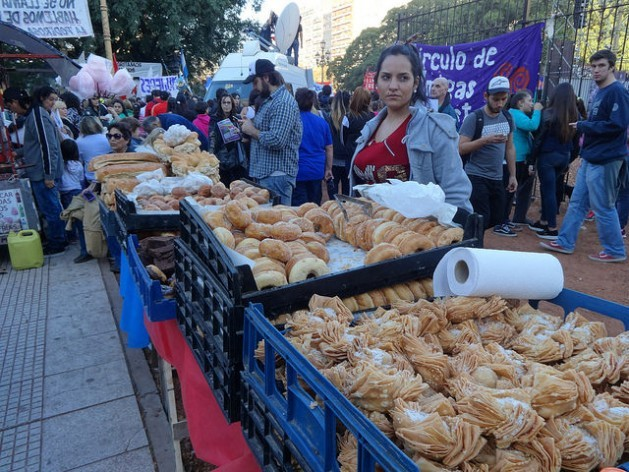 A young street vendor sells typical Argentine baked goods in a market near the Plaza de los dos Congresos, in Buenos Aires. Credit: Fabiana Frayssinet/IPS