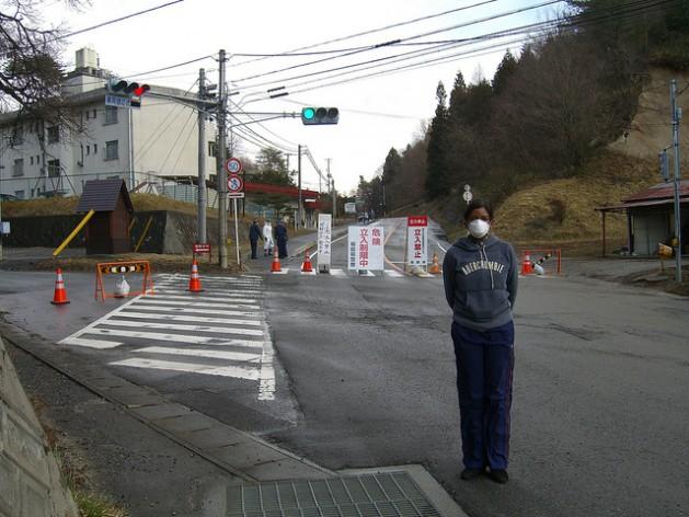 A reporter stands at a roadblock outside Fukushima's 20 kilometre exclusive zone in March 2011. Credit: Suvendrini Kakuchi/IPS