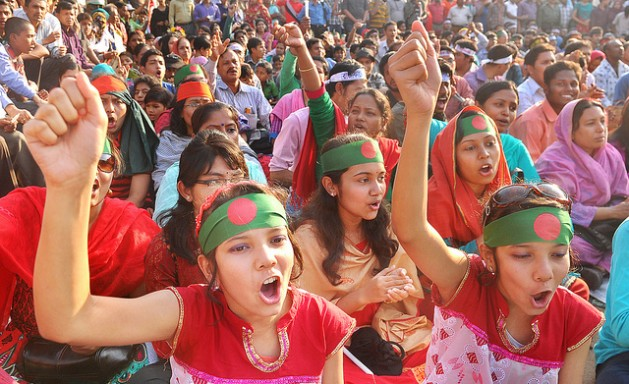 Young Bangladeshi women raise their fists at a protest in Shahbagh. Credit: Kajal Hazra/IPS