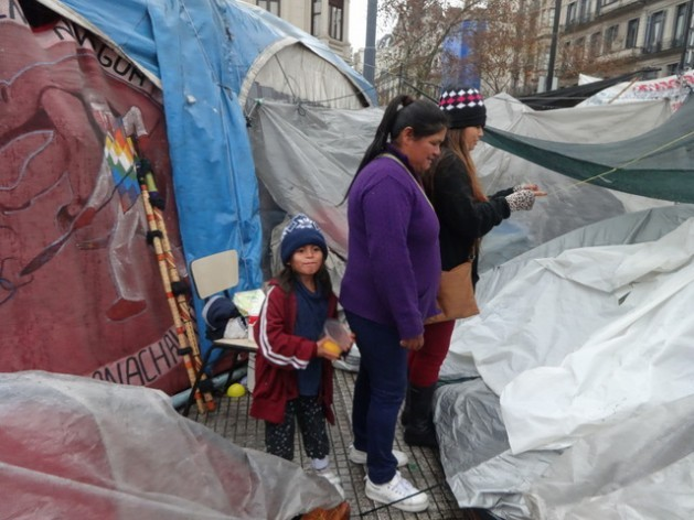 Ernestina Moreno of the Wichi indigenous community and her daughter and granddaughter look over part of the camp in a small Buenos Aires square where native demonstrators from the northern Argentine province of Formosa have been protesting since February, demanding recognition of their collective land ownership. Credit: Fabiana Frayssinet/IPS