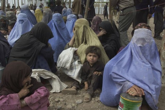 A group of refugee women and their children await the arrival of Secretary-General Kofi Annan at the Shamshatoo camp in December 2001. The camp, at a frontier province in north-west Pakistan, served as temporary home to some 70,000 Afghan refugees fleeing fighting between the United Front and the Taliban. Credit: UN Photo/Eskinder Debebe