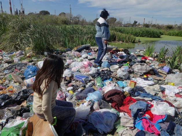 Nora Pavón and one of her daughters in the informal garbage dump behind their home. The swamp acts as a sewer in Villa Inflamable, in the suburb of Avellaneda on the south side of Buenos Aires. Credit: Fabiana Frayssinet/IPS