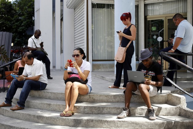 A group of people outside the medical library in the central Havana neighourhood of El Vedado, where Wi-Fi connection is now available. It is one of the 35 hotspots opened by the government telecoms monopoly around the country. Credit: Jorge Luis Baños/IPS