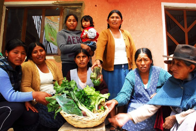 Women from the Sucre Association of Urban Producers, who are from poor neighbourhoods on the outskirts of Bolivia's official capital, with a basketful of ecologically grown fresh vegetables from their greenhouses, which have improved their families' diets and incomes. Credit: Franz Chávez/IPS