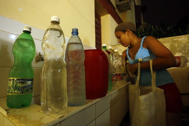 A resident of the East Havana municipality arranges the containers of drinking water that she has brought home, after days without piped water in her home in the Cuban capital. Fetching water for household use has been added to the day-to-day tasks of women in Havana. Credit: Jorge Luis Baños/IPS