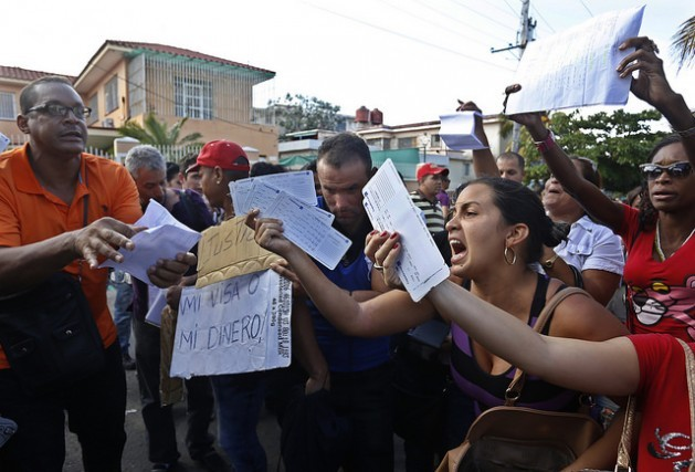 Hundreds of Cubans gathered outside the Ecuadorean embassy in Havana in an infrequent public display of discontent, protesting Quito's decision to require that Cubans visiting Ecuador obtain a visa. Many held up the airplane tickets they had already bought, asking to be given visas or to be reimbursed for the money they had spent. Credit: Jorge Luis Baños/IPS