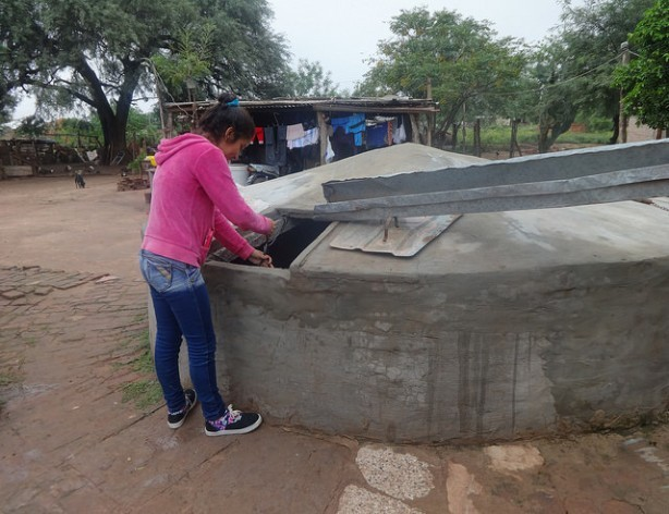 Jésica Garay, a young mother who is studying to become a teacher, gets water from the family tank built next to her humble home in the rural municipality of Corzuela in the northeast Argentine province of Chaco. Credit: Fabiana Frayssinet/IPS
