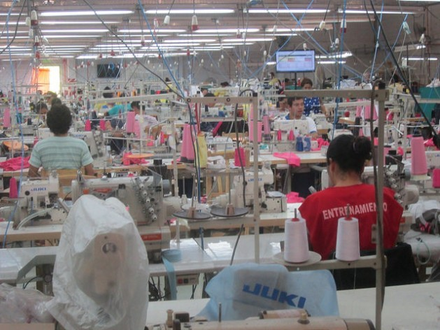 """Texcin, the garment plant built by Brazilian company Riachuelo near the airport in Asunción, under Paraguay's maquila law, which offers tax exemptions and other incentives for export-oriented production. In the foreground a garment worker in training (""""entrenamiento""""). Credit: Mario Osava/IPS"""
