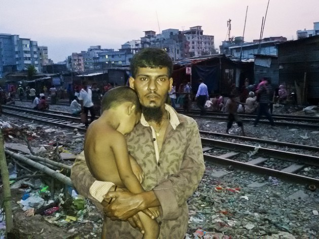 Abdul Aziz stands with one of his children in Dhaka's Malibagh slum. He came here a decade ago after losing everything to river erosion, hoping to rebuild his life, but has found only grinding poverty. Credit: Rafiqul Islam/IPS