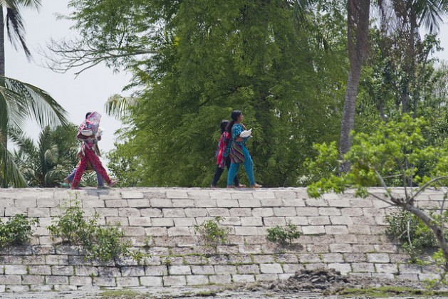 Girls walk across an embankment in the Satkhira district of Bangladesh. The height of the polders needs to be increased to save coastal populations from storm surges and cyclones. Credit: Rafiqul Islam/IPS