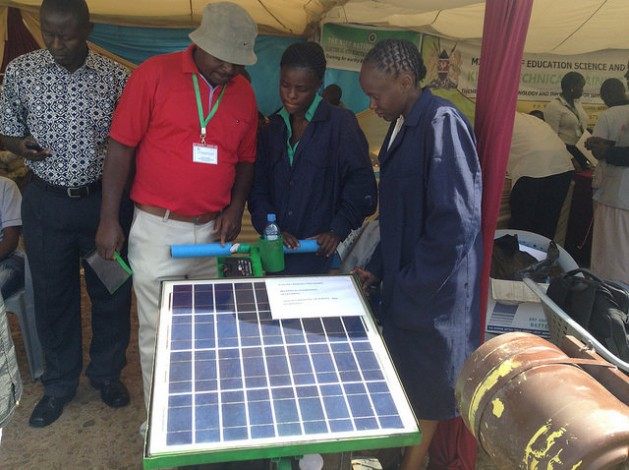 A solar-powered mower on display with its inventors, Kenyan university engineering students Emma Masibo (left) and Lucy Bwire, with their lecturer Peter Wamalwa. The mower was exhibited during the 5th National Science Week that opened on May 16, 2016 in Nairobi. Young people are using innovation to protect the environment and make life easier. Credit: Justus Wanzala/IPS