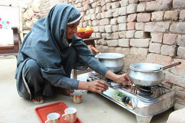 Nabela Zainab prepares tea on the biogas stove in her home in Faisalabad, Pakistan. The stove has eased indoor air pollution and restored her health. Credit: Saleem Shaikh/IPS