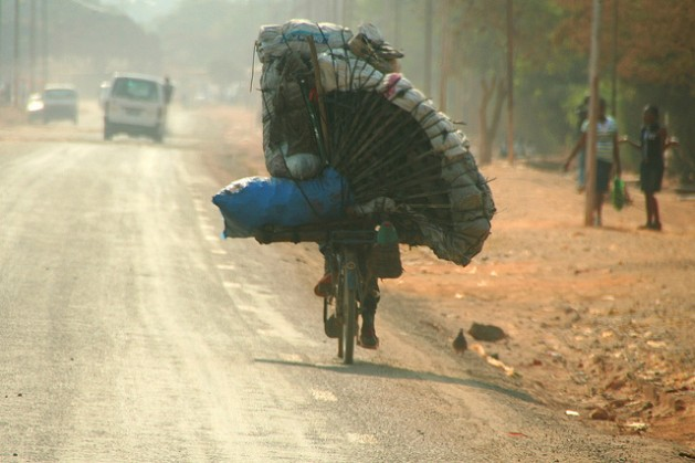A Congolese man transports charcoal on his bicycle outside Lubumbashi in the DRC. An estimated 138 million poor households spend 10 billion dollars annually on energy-related products such as charcoal, candles, kerosene and firewood. Credit: Miriam Mannak/IPS
