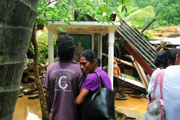 Family members wait near a house buried by the landslide as rescue workers look for survivors. Credit: Amantha Perera/IPS