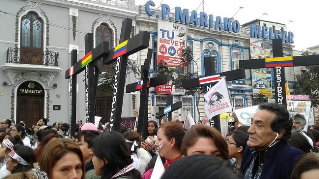 A group of demonstrators with black crosses, symbolising the victims of femicide in Peru and other countries of Latin America, march down a street in the centre of Lima during an Aug. 13 march against gender violence. Credit: Noemí Melgarejo/IPS