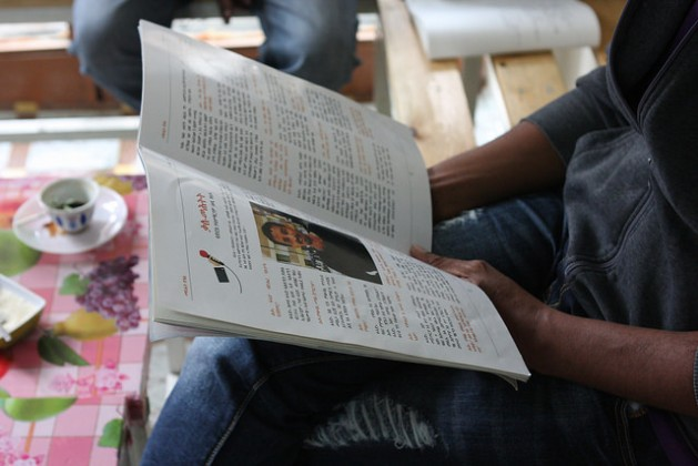 Eritrean journalist Estifo displaying Tsilal, the magazine he edits, which deals with the risks of migration and difficult reality of being in Europe. Credit: James Jeffrey/IPS