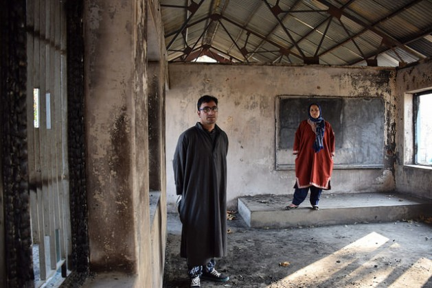 Shugufta Barkat, a former teacher, and her brother Rasikh Barkat, a former student, stand the charred remains of the Nasirabad Government High School in Kulgam – one of the many schools in India's Kashmir that have been recently burnt down. Credit: Stella Paul/IPS