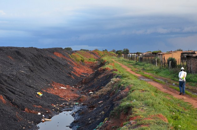 The Masakane village in Mpumalanga sits mere meters away from coal heaps feeding Duvha Power Station. The formal coal industry has failed to bring economic opportunities to local communities, so many residents turn to informal coal mining for an income. Credit: Mark Olalde/IPS