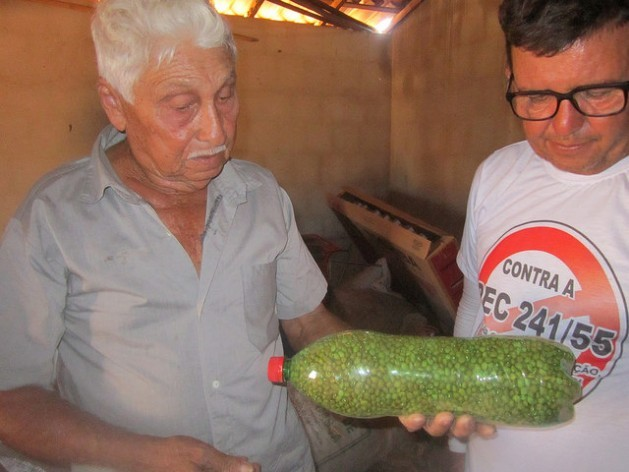 Raimundo Pinheiro de Melo, better known as Mundinho, a 76-year-old farmer who lives in the Apodi municipality in Northeast Brazil, shows a visiting farmer a bottle of bean seeds which he stores and protects. Credit: Mario Osava/IPS