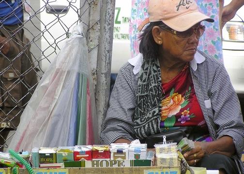 A cigarette vendor in Manila sells a pack of 20 sticks for less than a dollar. Credit: Kara Santos/IPS