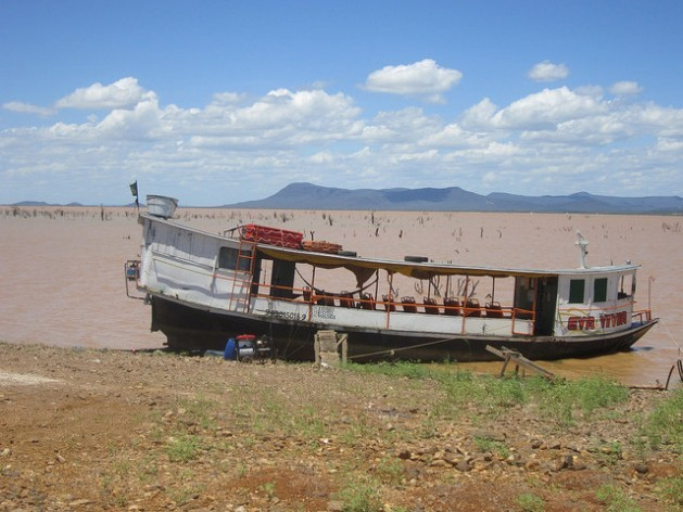 A boat under repair on the shore of the Sobradinho reservoir, which has a low water level due to the five years of drought which has plagued the semi arid interior of Northeastern Brazil. Bushes submerged by the dammed-up waters of the São Francisco river since the 1970s can be glimpsed. Credit: Mario Osava/IPS