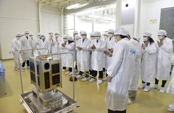Filipino scientists and engineers with their Japanese counterparts look at the completed Diwata-1. Credit: Philippine Microsatellite Program