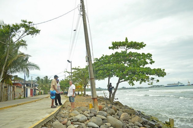 Reynaldo Charles and Ezequiel Hudson talk with Eliécer Quesada (left to right) about the state of the breakwater on which they are standing. This is the part where the waves reach closest to the houses, and at high tide the water crosses over the new bicycle lane and the street and reaches the homes, in the town of Cienaguita on Costa Rica's Caribbean coast. Credit: Diego Arguedas/IPS