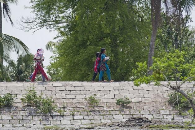 Girls walk across an embankment in the Satkhira district of Bangladesh. Credit: Rafiqul Islam/IPS